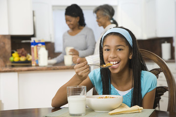 African girl eating breakfast in kitchen