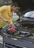 African woman checking oil in car engine