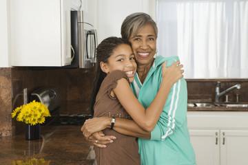 African grandmother hugging granddaughter