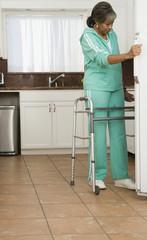 Senior African woman with walker looking refrigerator