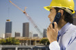 Hispanic businessman in hard hat talking on cell phone
