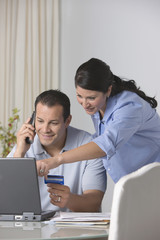 Hispanic couple paying bills online with credit card