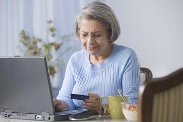 Senior Hispanic woman shopping online with credit card