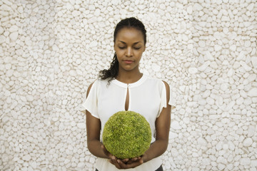 African woman holding round plant