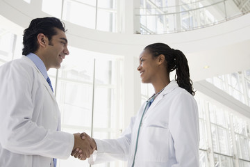 Male and female doctors shaking hands
