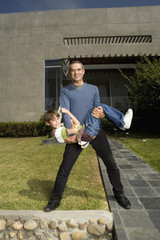Hispanic father and son playing in front of house