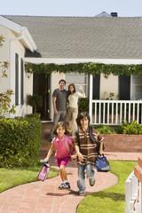 Hispanic parents waving at children leaving for school