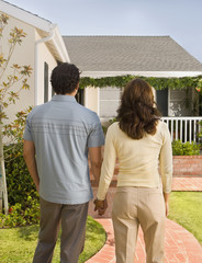 Rear view of Hispanic couple holding hands in front of house