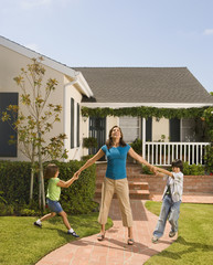 Hispanic children pulling on mother's arms in front of house