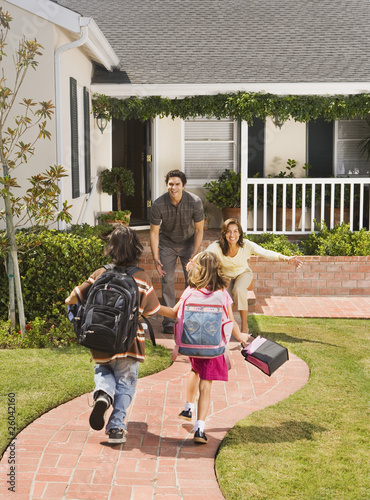 Hispanic parents greeting children coming home from school