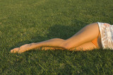 Woman with bare legs laying in grass
