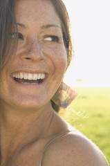 Portrait of woman in sunlit meadow