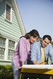 Hispanic couple looking at blueprints outdoors
