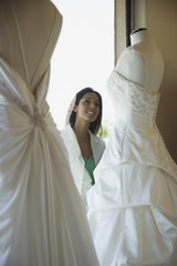 Hispanic woman looking at wedding dress through window
