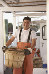 Hispanic fisherman carrying basket