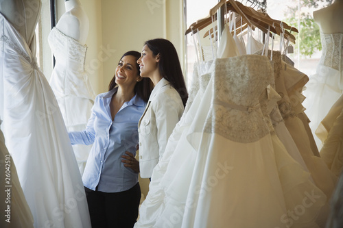 Hispanic sisters looking at wedding dresses in shop