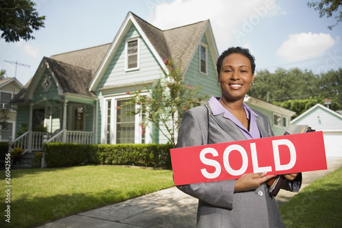 African woman holding Sold sign in front of house