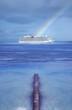 Cruise ship on horizon at end of rainbow