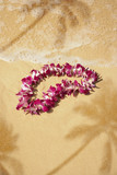Flower lei on sand with palm tree shadows