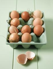 Eggs in carton next to broken egg shell