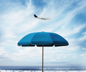 Airplane flying over beach umbrella