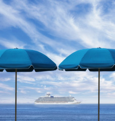 Cruise ship on horizon between two beach umbrellas