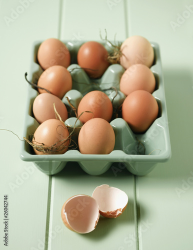 Eggs in carton next to broken egg shell