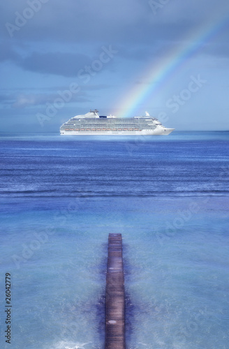 Cruise ship on horizon at end of rainbow
