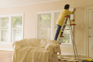 Hispanic man on ladder painting