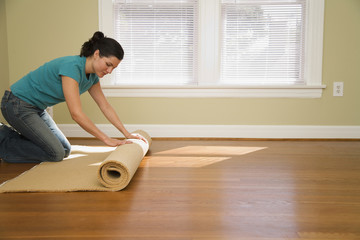 Hispanic woman unrolling carpet in new home