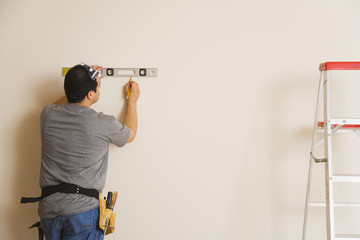 Hispanic man measuring with level on wall