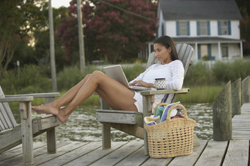 African woman using laptop on dock