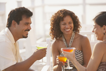 Hispanic friends drinking cocktails outdoors