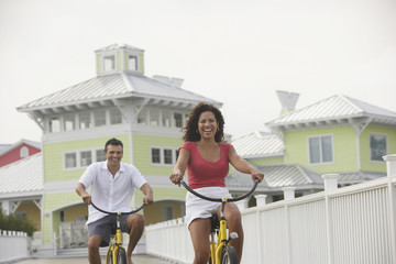 Hispanic couple riding bicycles on boardwalk