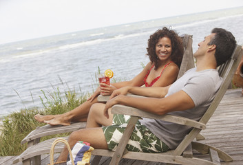 Hispanic couple sitting in lounge chairs at beach