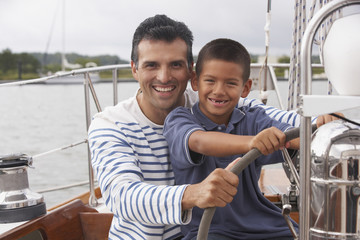 Hispanic father and son steering sailboat