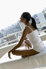 African woman meditating on balcony