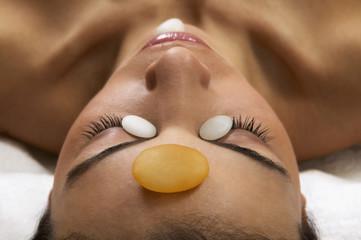 Close up of Hispanic woman receiving stone spa treatment