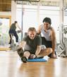 Trainer helping man stretch in health club