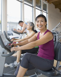Asian woman riding exercise bike in health club