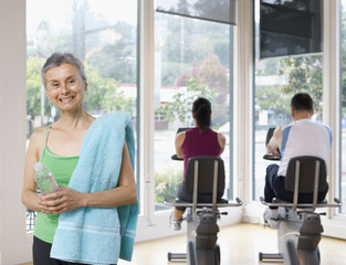 Hispanic woman with towel and water bottle in health club