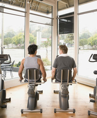Rear view of two men using exercise bikes