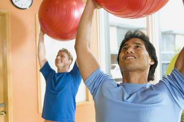Two men exercising with fitness balls in health club