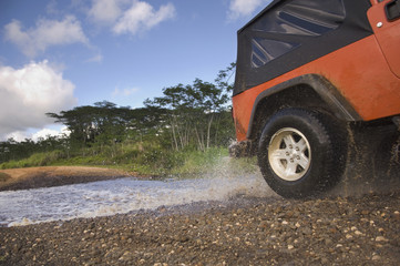 4x4 driving through water on remote road