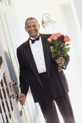 African man in tuxedo with bouquet of flowers