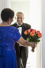 African man in tuxedo giving bouquet of flowers to woman