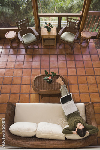 High angle view of woman using laptop on sofa