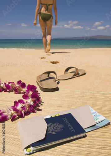 Woman walking away from passport and sandals on beach