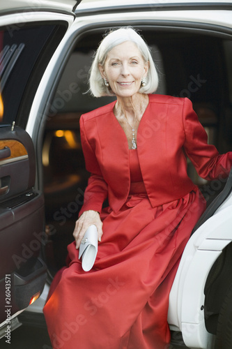 Well dressed senior woman sitting in limousine