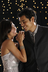 Hispanic couple dressed for night out with lights in background